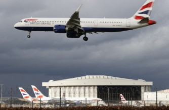 """A British Airways aircraft flies over parked British Airways planes on the tarmac at London Heathrow Airport in west London on February 5, 2021. - Britain confirmed Thursday it will introduce its new mandatory hotel quarantine rules for travellers returning from dozens of countries deemed at """"high risk"""" from Covid-19 variants later this month. The policy, which will begin from February 15, will require all UK citizens and permanent residents returning from countries on its so-called travel ban list to self-isolate in a government approved facility for 10 days. (Photo by Adrian DENNIS / AFP)"""