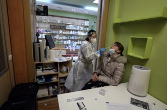 A pharmacist conducts an antigen rapid test for COVID-19 at her pharmacy in Madrid on February 09, 2021. - The total number of confirmed coronavirus cases in Spain, one of Europe's hardest-hit nations, has topped three million since the start of the pandemic, the health ministry said. (Photo by OSCAR DEL POZO / AFP)