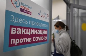 A woman enters a vaccination point to receive an injection of Russia's Sputnik V (Gam-COVID-Vac) vaccine against the coronavirus disease in a public services office in Moscow on February 10, 2021. (Photo by NATALIA KOLESNIKOVA / AFP)