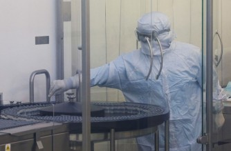 An employee using personal protective equipment (PPI) works during the production of vaccines against Covid-19 at the Osvaldo Cruz Foundation (FIOCRUZ), in Rio de Janeiro, Brazil, on February 12, 2021. - In this phase of the production, the first doses of the vaccine are being bottled and sent to the quality control department before being released for vaccination. (Photo by Andre Coelho / AFP)
