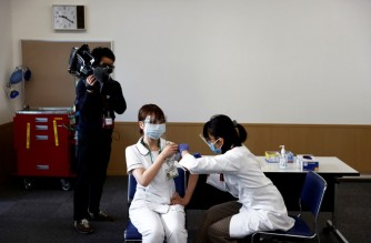 A medical worker (C) receives a dose of the COVID-19 vaccine as the country launches its inoculation campaign at the Tokyo Medical Center in Tokyo on February 17, 2021. (Photo by Behrouz MEHRI / POOL / AFP)