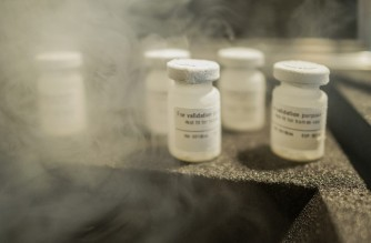 Specimens of premixed saline solution designed to mimic the a COVID-19 vaccine are seen on the top of a prototype of Cryo-Vacc, an ultra-cold biologic transport unit, in Dunkeld West, Johannesburg, on February 17, 2021. - The unit uses a helium based refrigerating technology, has been created to safely transport COVID-19 vaccines doses (6000 per unit) as well as other vaccines, especially in rural area of the Africa continent as it maintain the temperature inside (8 to -150 C) constant for over three weeks without an external power source. (Photo by LUCA SOLA / AFP)
