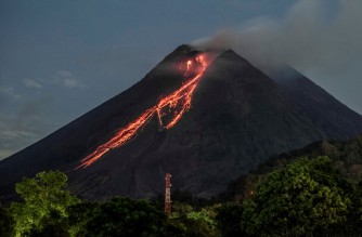 Lava flows down from the crater of Mount Merapi as seen from Kaliurang, in Yogyakarta on February 19, 2021. (Photo by AGUNG SUPRIYANTO / AFP)