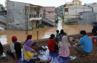 Flood-affected residents sit on higher ground in Jakarta on February 20, 2021, following heavy overnight rains. (Photo by DASRIL ROSZANDI / AFP)