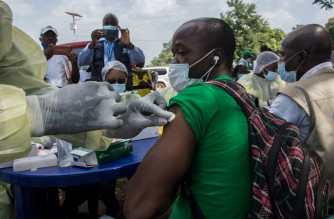 A health worker from the Guinean Ministry of Health cleans a suspected contact of an Ebola patient's arm ahead of administering an anti-Ebola vaccine in Gueckedou, Guinea, on February 23, 2021. - Guinea launched an Ebola vaccination campaign on February 23, 2021, after a fresh outbreak of the deadly disease struck the country this month, with officials hoping to eradicate the virus in six weeks. (Photo by CAROL VALADE / AFP)