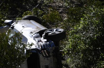 """The vehicle driven by golfer Tiger Woods lies on its side in Rancho Palos Verdes, California, on February 23, 2021, after a rollover accident. - US golfer Tiger Woods was hospitalized Tuesday after a car crash in which his vehicle sustained """"major damage,"""" the Los Angeles County Sheriff's department said. Woods, the sole occupant, was removed from the wreckage by firefighters and paramedics, and suffered """"multiple leg injuries,"""" his agent said in a statement to US media. (Photo by Patrick T. FALLON / AFP)"""