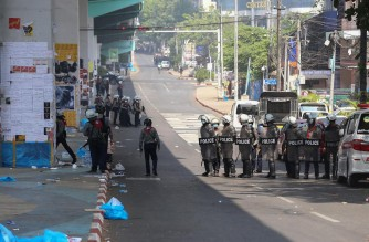 Riot police gather on a road during protests against the military coup in Yangon on February 26, 2021. (Photo by STR / AFP)