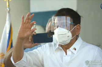 President Rodrigo Duterte is seen here inspecting a vial of the Sinovac vaccine, CoronaVac, shortly after the boxes containing the vaccine doses were offloaded from a Chinese military plane that arrived in the country on Sunday afternoon, Feb. 28, 2021.  The 600,000 vaccine doses were donated by the Chinese government to the Philippines.  (Screenshot pf RTVM video/Courtesy RTVM)