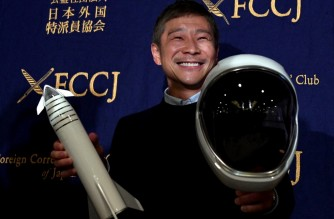 Yusaku Maezawa, entrepreneur and CEO of ZOZOTOWN and SpaceX BFR's first private passenger, poses with a miniature rocket and space helmet prior to start of a press conference at the Foreign Correspondents' Club of Japan in Tokyo on October 9, 2018. - It was confirmed in September that Maezawa will be the first man to fly around the moon on a SpaceX rocket as early as 2023. (Photo by Toshifumi KITAMURA / AFP)