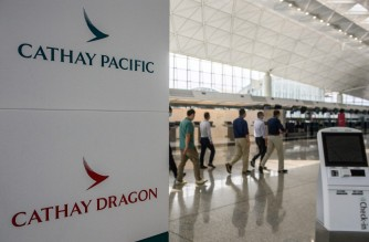 People walk past signage for Cathay Pacific and Cathay Dragon near the city's flagship carrier check-in counters at Hong Kong International Airport on October 20, 2020. (Photo by Anthony WALLACE / AFP)