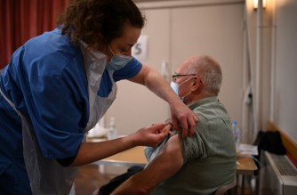 Nurse Sally Griffiths (L) administers an injection of AstraZeneca/Oxford Covid-19 vaccine to a patient at the vaccination centre set up at St Columba's church in Sheffield, northern England, on February 20, 2021. (Photo by Oli SCARFF / AFP)