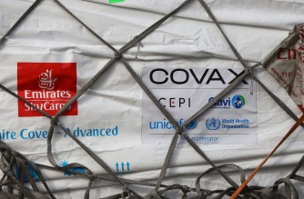 This photograph taken on February 24, 2021 shows an Emirates Airlines logo next to a Covax tag on a shipment of Covid-19 vaccines from the Covax global Covid-19 vaccination programme, at the Kotoka International Airport in Accra. - Ghana received the first shipment of Covid-19 vaccines from Covax, a global scheme to procure and distribute inoculations for free, as the world races to contain the pandemic. Covax, launched last April to help ensure a fairer distribution of coronavirus vaccines between rich and poor nations, said it would deliver two billion doses to its members by the end of the year. (Photo by Nipah Dennis / AFP)