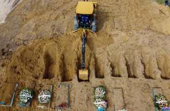 (FILES) This file photo taken on January 08, 2021 shows an aerial view of a tractor digging graves in a new area of the Nossa Senhora Aparecida cemetery reserved for COVID-19 victims, in Manaus, Brazil. - Brazil registers record of 1,641 Covid-19 deaths in 24 hours, on March 2, 2021, according to official sources. (Photo by Michael DANTAS / AFP)