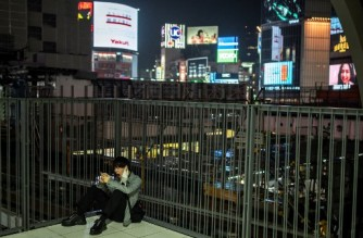 A man sitting on the ground yawns at Shibuya area in Tokyo on March 5, 2021 as officials extended the Covid-19 coronavirus state of emergency by a fortnight. (Photo by Charly TRIBALLEAU / AFP)