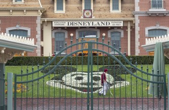 (FILES) In this file photo taken on March 14, 2020 an employee cleans the grounds behind the closed gates of Disneyland Park on the first day of the closure of Disneyland and Disney California Adventure theme parks as fear of the spread of coronavirus continue, in Anaheim, California - California on March 5, 2021 paved the way for Disneyland, other theme parks and outdoor stadiums to reopen sooner than expected as it relaxed reopening criteria, the state health department said. (Photo by DAVID MCNEW / AFP)