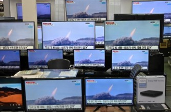 Television screens show file footage of North Korea's missile test as a news programme broadcasts reports about North Korea's suspected ballistic missile test, at an electronics mall in Seoul on March 25, 2021. (Photo by Jung Yeon-je / AFP)