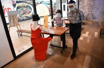 (File photo) A staff member of a restaurant walks past mannequins wearing face masks and face shields displayed inside a restaurant, to simulate seating arrangements when restaurants will once again be allowed to cater to dine-in customers, in a mall in Manila on June 2, 2020, a day after the government eased up quarantine measures aimed at preventing the spread of the COVID-19 novel coronavirus in the country's capital. - Manila emerged on June 1 from one of the world's longest coronavirus lockdowns as the Philippines seeks to repair its badly damaged economy even as the number of new infections surges. (Photo by Ted ALJIBE / AFP)