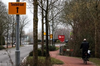 A man cycles by a panel indicating the direction of the Covid-19 testing centre in Bovenkarspel, northern Netherlands, targeted, earlier in the day, by the explosion of an homemade explosive device that caused only material damage, according to the police, on March 3, 2021. - The incident took place in an area close to where a testing centre was burnt down last January, in the village of Urk in the province of Flevoland, Netherlands, when the curfew came into effect in order to fight the Covid-19 epidemic. (Photo by Aris Oikonomou / AFP)