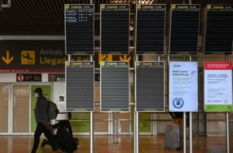 "Travellers walk at the Terminal 4 of Adolfo Suarez Barajas airport in Madrid, on March 23, 2021. - Spain will on March 30 lift restrictions on arrivals from Britain that have been in place since December to prevent the spread of new coronavirus strains, government spokeswoman Maria Jesus Montero said. Restrictions on arrivals from Brazil and South Africa will be extended until April 13 but ""not those with Britain"" because the country's vaccination campaign is very advanced, she told a news conference. (Photo by GABRIEL BOUYS / AFP)"