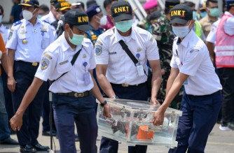 Indonesian officials carry a box contain cockpit voice recorder (CVR or blackbox) at the port in Tanjung Priok in Jakarta, on March 31, 2021, after it was recovered during search operations for the Sriwijaya Air Boeing 737-500 passenger jet which disappeared after taking off from Jakarta's international airport on January 9. (Photo by BAY ISMOYO / AFP)