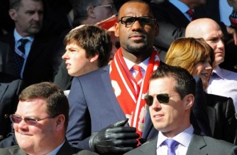 "(FILES) In this file photo taken on October 15, 2011, US basketball player Lebron James (C), a minority owner at Anfield, looks on before the English Premier League football match between Liverpool and Manchester United at Anfield in Liverpool, England.  RESTRICTED TO EDITORIAL USE. No use with unauthorized audio, video, data, fixture lists, club/league logos or ""live"" services. Online in-match use limited to 45 images, no video emulation. No use in betting, games or single club/league/player publications. - NBA superstar James has increased his ownership stake in English Premiership club Liverpool via a deal confirmed on March 31, 2021, that makes him a partner in Fenway Sports Group. (Photo by Andrew YATES / AFP)"