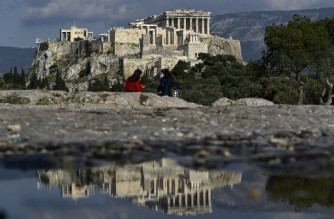 People enjoy a sunny afternoon on a hill overlooking the ancient Acropolis in Athens on April 1, 2021, a day after Greece said it would reopen most shops and relax leisure restrictions despite persistently high Covid-19 deaths and infections that have put its health system under major strain. (Photo by Louisa GOULIAMAKI / AFP)