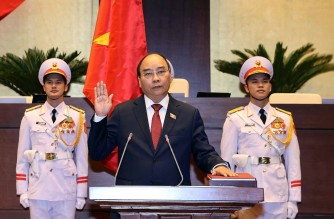 This picture taken and released by the Vietnam News Agency on April 5, 2021 shows former prime minister and Vietnam's newly elected President Nguyen Xuan Phuc (C) taking oath during the National Assembly's spring session in Hanoi. (Photo by STR / Vietnam News Agency / AFP)