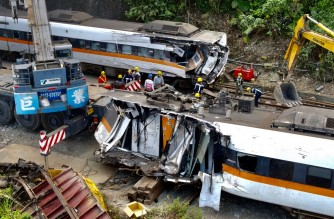 An aerial view shows workers checking damaged carriages at the site of a derailed train accident on the mountains of Hualien, eastern Taiwan on April 6, 2021. (Photo by Sam Yeh / AFP)