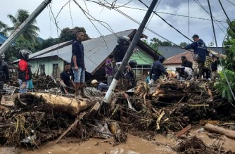 In this picture taken on April 7, 2021 residents check through debris near damaged homes in Waiwerang village of East Flores following torrential rains from Tropical Cyclone Seroja. - Indonesian navy ships packed with aid arrived on April 8 in a cyclone-ravaged section of the archipelago, as the death toll from the disaster rose to above 200 people, including dozens killed in neighbouring East Timor. (Photo by Alfred Ike Wurin / AFP)