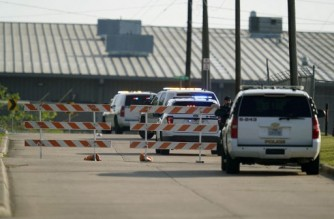 """A Bryan police officer blocks access to an industrial park near the scene of a mass shooting in Bryan, Texas on April 8, 2021. - One person was dead and several in critical condition following a shooting at a business in Texas Thursday, just hours after US President Joe Biden called gun violence an """"epidemic"""" and unveiled plans to tackle the crisis. The suspect was """"in custody,"""" according to the police department in the east Texas town of Bryan where the attack took place. Officials said the individual shot and wounded one officer following the incident and was an employee of the cabinetry manufacturer where he carried out the shooting. (Photo by Sam Craft / AFP)"""