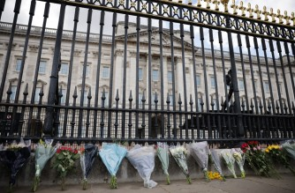 Floral tributes are seen laid against the railings at the front of Buckingham Palace in central London on April 9, 2021 after the announcement of the death of Britain's Prince Philip, Duke of Edinburgh. - Queen Elizabeth II's husband Prince Philip, who recently spent more than a month in hospital and underwent a heart procedure, died on April 9, 2021, Buckingham Palace announced. He was 99. (Photo by Tolga Akmen / AFP)