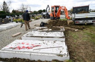 (FILES) In this file photo taken on March 30, 2020, employees of a funeral home company install fifteen new burial vaults in a cemetery near Bethune as the peak of the epidemic of Covid-19 is set to hit the country. - France is about to surpass the grim milestone of 100,000 official coronavirus victims, amid a third wave of infections. (Photo by DENIS CHARLET / AFP)
