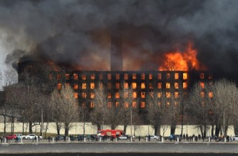 Firefighters work to extinguish a fire in a historic factory in Saint Petersburg on April 12, 2021. - Russia on April 13, 2021 detained two people after a huge fire gutted a historic factory in Saint Petersburg, as firefighters continued putting out the blaze. A fire broke out over several floors of the red-brick Nevskaya Manufaktura building in Russia's second city. The inferno killed one firefighter and left two more hospitalised with serious burns. (Photo by Olga MALTSEVA / AFP)