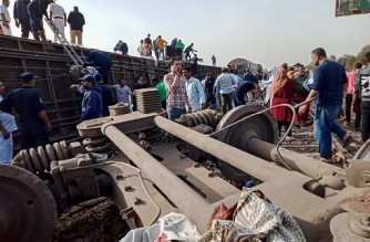 People gather at the scene of a railway accident in the city of Toukh in Egypt's central Nile Delta province of Qalyubiya on April 18, 2021. - The train accident north of Cairo on April 18 left 11 people dead and 98 others injured, after it derailed off its tracks heading northwards from the capital Cairo, the health ministry said, in the latest railway disaster. Eight carriages derailed off the tracks as the train headed to Mansoura, about 130 kilometres north of Cairo. (Photo by - / AFP)