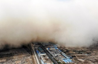 This aerial photo taken on April 25, 2021 shows a sandstorm engulfing a village in Linze county, in the city of Zhangye in China's northwestern Gansu province. (Photo by STR / CNS / AFP) / China OUT
