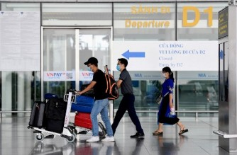 Passengers walk with their luggage at the departure terminal at Noi Bai International Airport in Hanoi on September 16, 2020. - Vietnam said September 16 it will resume international commercial flights to and from six Asian destinations, months after a suspension due to the COVID-19 coronavirus. (Photo by Nhac NGUYEN / AFP)
