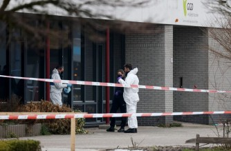 """Police blocks a street as forensic sweeps for evidence after an explosion took place at a COVID-19 testing centre in the town of Bovenkarpsel on March 3, 2021. - An explosion struck a Dutch coronavirus test centre in a """"cowardly act of destruction"""" on March 3, shattering windows but causing no injuries, police and government officials said. The early morning blast in the town of Bovenkarspel, 60 kilometres (40 miles) north of the capital Amsterdam, was caused by a metal cylinder left outside the building, police said. (Photo by Aris Oikonomou / AFP)"""