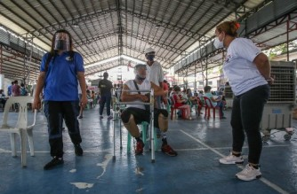Elderly residents wait for their turn to get the AstraZeneca vaccine against Covid-19 in Manila on March 30, 2021, after the government imposed stricter lockdown, as hospitals in the capital struggle to cope with a surge in coronavirus infections. (Photo by Jam STA ROSA / AFP)