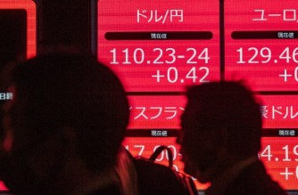 People walk past an electronic quotation board displaying the Japanese yen's exchange rate against the US dollar (top L) after it broke the 110 yen mark for the first time since March 2020, at the Tokyo Stock Exchange in Tokyo on March 30, 2021. (Photo by Philip FONG / AFP)