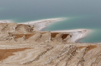 This picture taken from Jordan shows a partial view of the Dead Sea, which is dropping dramatically in height because of severe drought,  on April 20, 2021. - Experts say Jordan is now in the grip of one of the most severe droughts in its history, but many warn the worst is yet to come. The country's environment ministry says it is among the world's most four water-deficient countries, and fears that a heating planet will make the situation more severe. (Photo by Khalil MAZRAAWI / AFP)