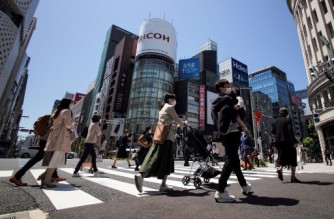 People cross a street at Tokyo's shipping district Ginza on April 26, 2021, during a new coronavirus state of emergency covering Tokyo, Osaka, Kyoto and Hyogo regions. (Photo by Kazuhiro NOGI / AFP)