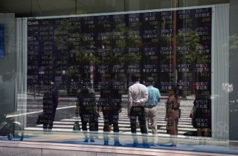 Pedestrians are reflected on an electronic board displaying Japanese companies' share prices of the Tokyo Stock Exchange in Tokyo on April 30, 2021. (Photo by Yuki IWAMURA / AFP)