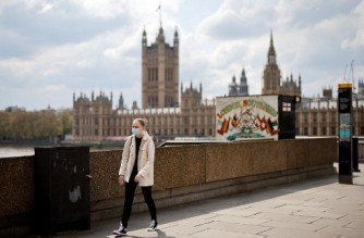 A person wearing a face covering due to Covid-19 walks near Houses of Parliament in central London on April 30, 2021. (Photo by Tolga Akmen / AFP)