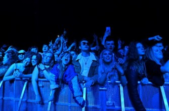 Fans watch Blossom perform at a live music concert hosted by Festival Republic in Sefton Park in Liverpool, north-west England on May 2, 2021, where a non-socially-distanced crowd of 5,000 are expected to attend. - A pilot programme to examine ways of putting on events in a post-covid-19 world will include a concert by the band Blossoms which will do away with social distancing, though audience members will have to provide proof of a negative coronavirus test before gaining entry. (Photo by Paul ELLIS / AFP)