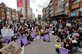 Women sit on the street to protest against a tax reform bill proposed by the government as the country battles its deadliest phase yet of the coronavirus pandemic, at the Bolivar Square in Bogota, on May 2, 2021. - Colombian President Ivan Duque asked the parliament to withdraw a tax reform bill that triggered four consecutive days of protests and riots and announced he will propose a new tax bill reform soon to the congress. (Photo by DANIEL MUNOZ / AFP)