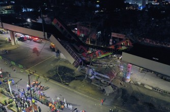 An aerial view shows rescue workers at the site of a metro train accident after an overpass for a metro partially collapsed in Mexico City on May 3, 2021. - At least 15 people were killed and dozens injured when an elevated metro line collapsed in the Mexican capital on May 3 as a train was passing, authorities said. (Photo by PEDRO PARDO / AFP)