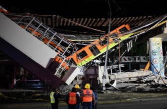 Rescue workers gather at the site of a train accident after an elevated metro line collapsed in Mexico City on May 4, 2021. (Photo by PEDRO PARDO / AFP)