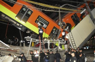 Rescue workers gather at the site of a metro train accident after an overpass for a metro partially collapsed in Mexico City on May 3, 2021. - An elevated metro line collapsed in the Mexican capital on Monday, leaving at least 23 people dead and dozens injured as a train came plunging down, authorities said. (Photo by Valentina ALPIDE / AFP)