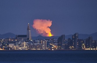 (FILES) This file photo taken on May 5, 2021 shows the skyline of the Icelandic capital Reykjavik with the glow from the lava coming out of a fissure near the Fagradalsfjall on the Reykjanes Peninsula behind. (Photo by Halldor KOLBEINS / AFP)