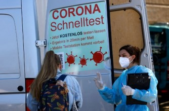 A medical worker speaks to a woman at a mobile Corona rapid test centre operating out of the back of a van parked at an entrance to the Tempelhofer Feld park on May 9, 2021 in Berlin as people made the most of the sunshine and temperature reaching 25 degrees Celsius amid the ongoing coronavirus COVID-19 pandemic. (Photo by David GANNON / AFP)